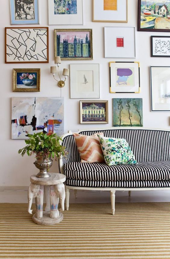 a fun and bold free form gallery wall with mismatching frames and without frames and various mismatching art