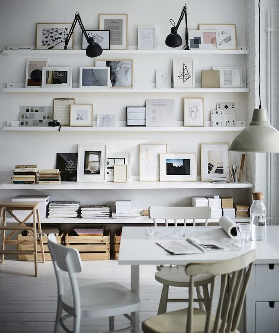 a gallery wall done IKEA ribba ledges, with various artworks and photos and matching floating shelves under the ledges for a cool look