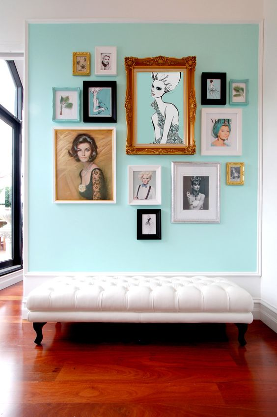 a glam free form gallery wall built around the central piece of art, with turquoise matting and mostly black and white or muted color art