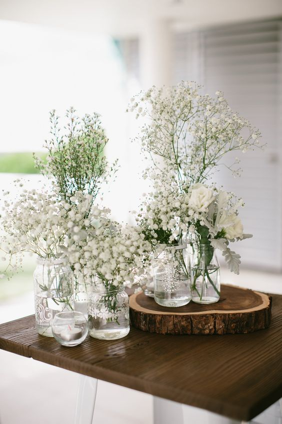 a gorgeous lovely white centerpiece of bottles and jars is a timeless idea for any spring tablescape
