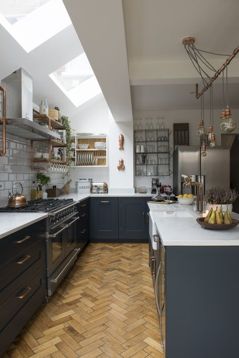 a graphite grey kitchen with white countertops, skylights, brass fixtures and hanging bulbs