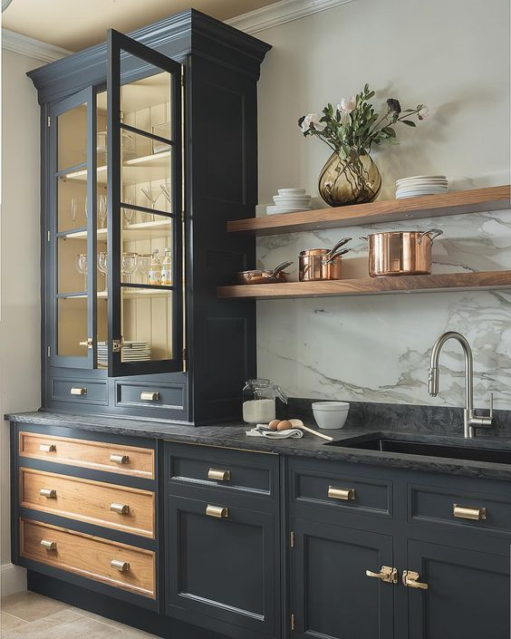 a graphite grey vintage kitchen with gold handles, a black stone countertop and a white stone backsplash
