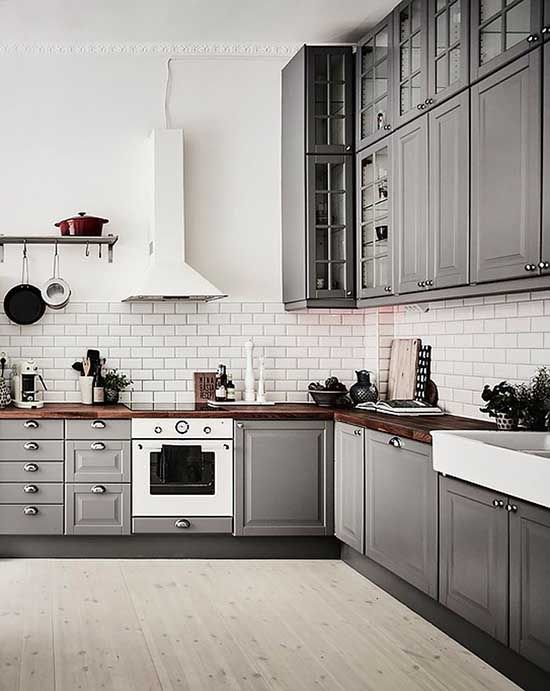 a grey Scandinavian kitchen with rich-stained butcherblock countertops and a white tile backsplash plus white appliances
