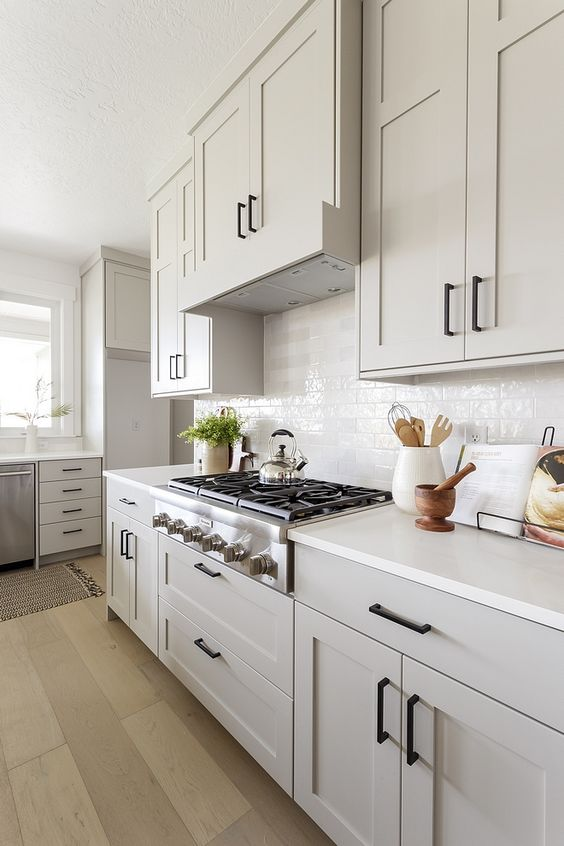 a grey farmhosue kitchen with shaker style cabinets, a white tile backsplash and white countertops plus black fixtures