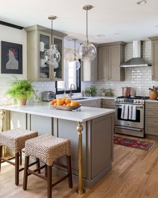 a grey farmhouse kitchen with a white countertop and a tile backsplash, glass bubble lamps and some art