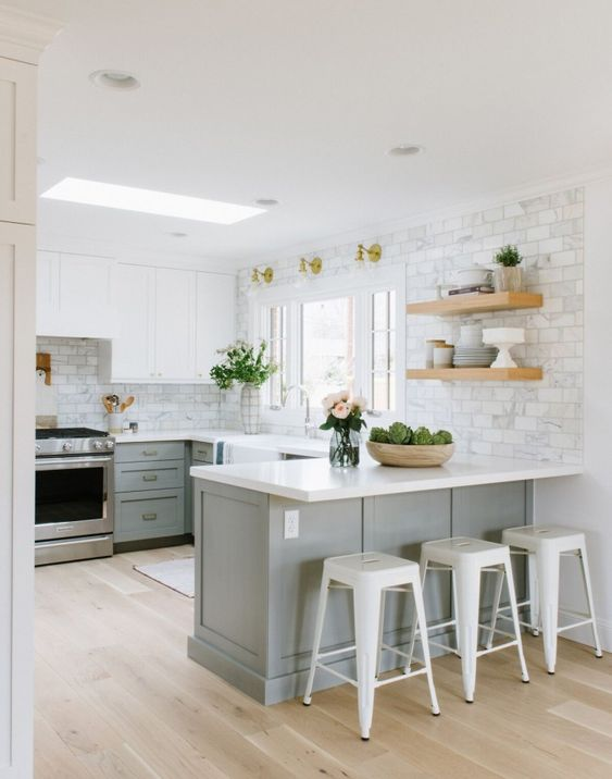 a grey farmhouse kitchen with a white marble tile backsplash and white tone countertops plus a skylight