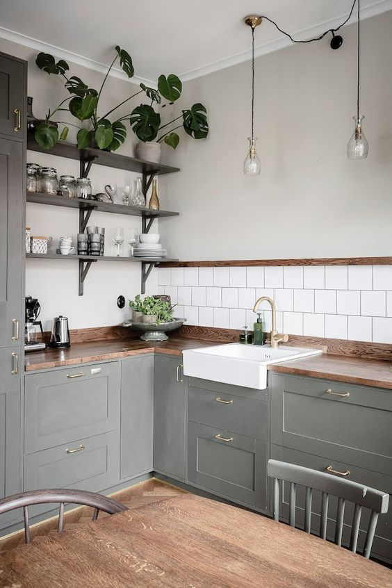 a grey rustic L-shaped kitchen with butcherblock countertops, open shelves and potted greenery plus pendant lamps