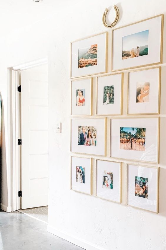 a grid gallery wall but with mismatching frames arranged in rows, with thin blonde wood frames and much matting