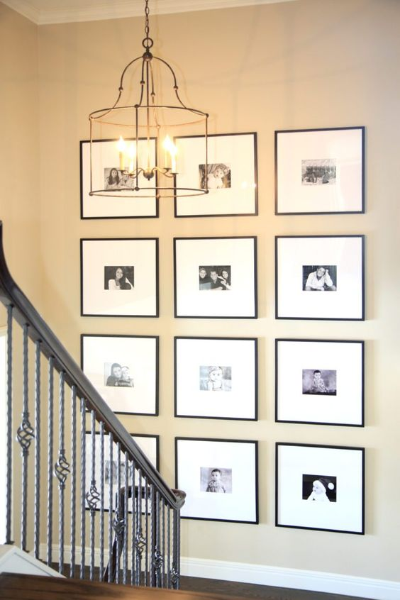 a grid gallery wall with family photos, black frames and white matting is a stylish and elegant way to style the space