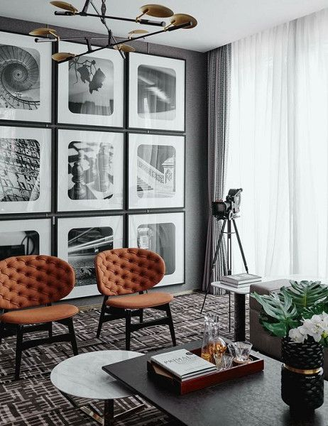 a grid gallery wall with thin black frames, white matting and black and white photos with curved angles feels retro chic