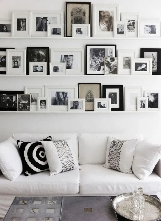 a large Scandinavian gallery wlal with white ledges, black and white artworks in various black and white frames