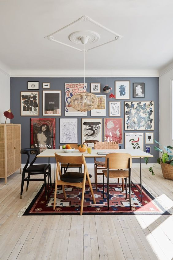 a large and bold free form gallery wall with thin frames and colorful art, mostly abstract, takes over the whole space