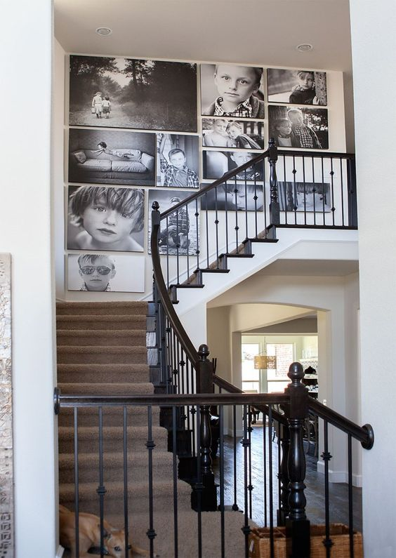 a large black and white gallery wall with oversized photos and no frames, with a free form is a cool and bold idea