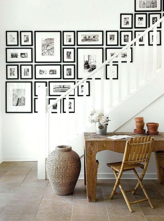 a large free form gallery wall with black frames and black and white prints is a stylish idea with an eclectic yet elegant feel