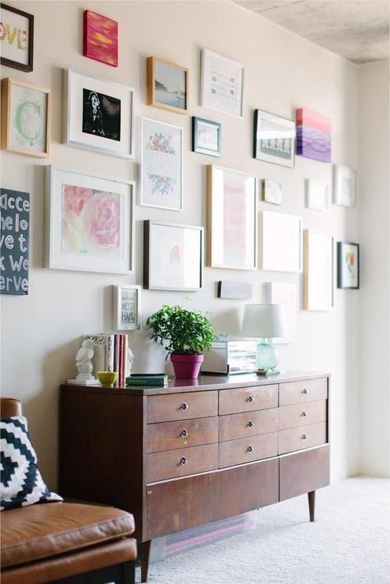 a large free form gallery wall with mismatching frames and various artworks and posters will bring an eclectic feel to the space