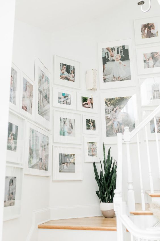 a large gallery wall done with IKEA Ribba ledges and colorful family photos with matting is amazing and very fresh