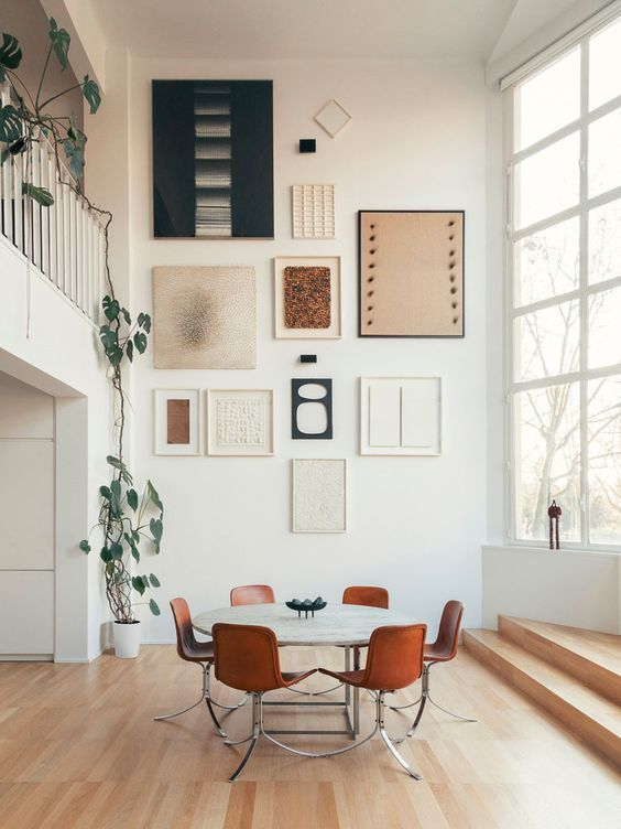 a large gallery wall with hin white, black and blonde wood frames and black, white and terracotta artworks