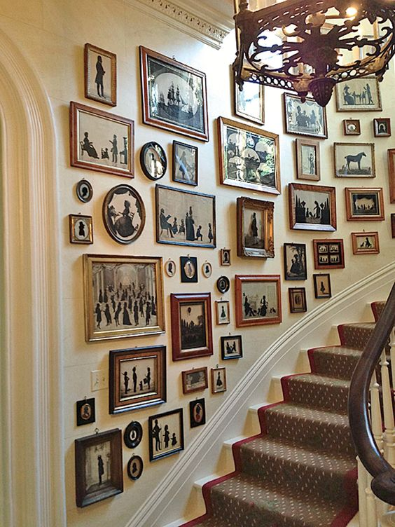 a large gallery wall with mismatching vintage frames and black and white artworks with a strong elegant vintage feel