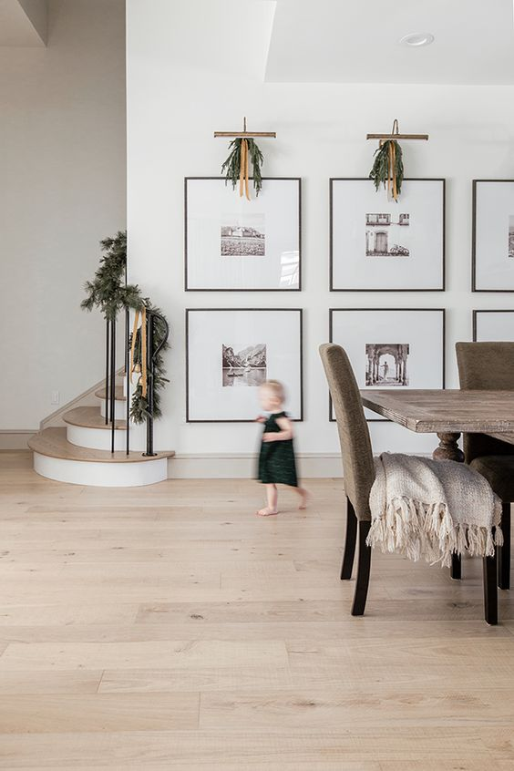 a large gallery wall with thin black frames, large matting and black and white photos is a very artful idea