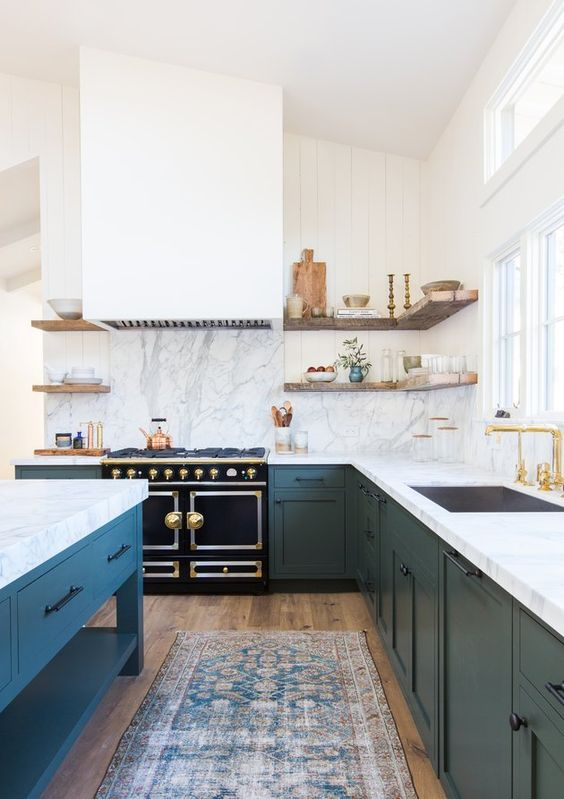 a large navy and white L-shaped kitchen with white stone countertops and a backsplash plus a matching kitchen island