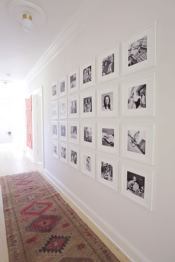 a large symmetrical gallery wall with matching white frames and black and white pictures of the family accents the long corridor