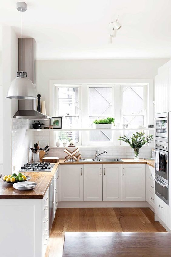 a light-filled white U-shaped kitchen with butcherblock countertops, a white pendant lamp and greenery