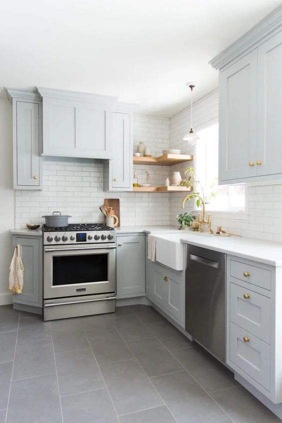 a light grey L shaped kitchen with open shelves, a white tile backsplash and gold handles is a very stylish and cozy space