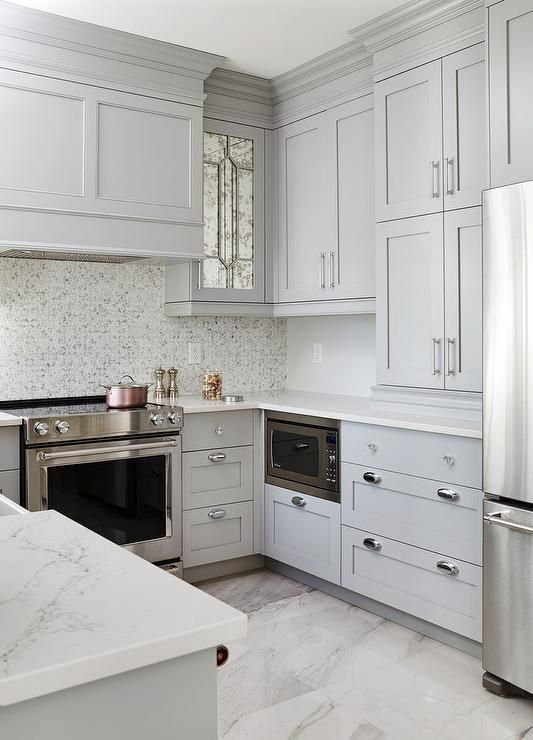a light grey farmhouse kitchen with a mosaic tile backsplash and white stone countertops is elegant and cool