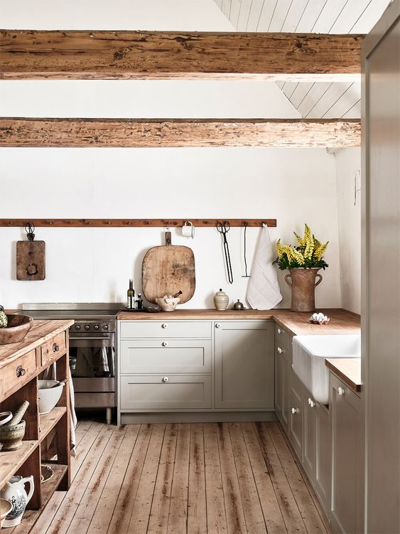 a light grey kitchen with butcherblock countertops and wooden beams, a wooden kitchen island and a wooden floor