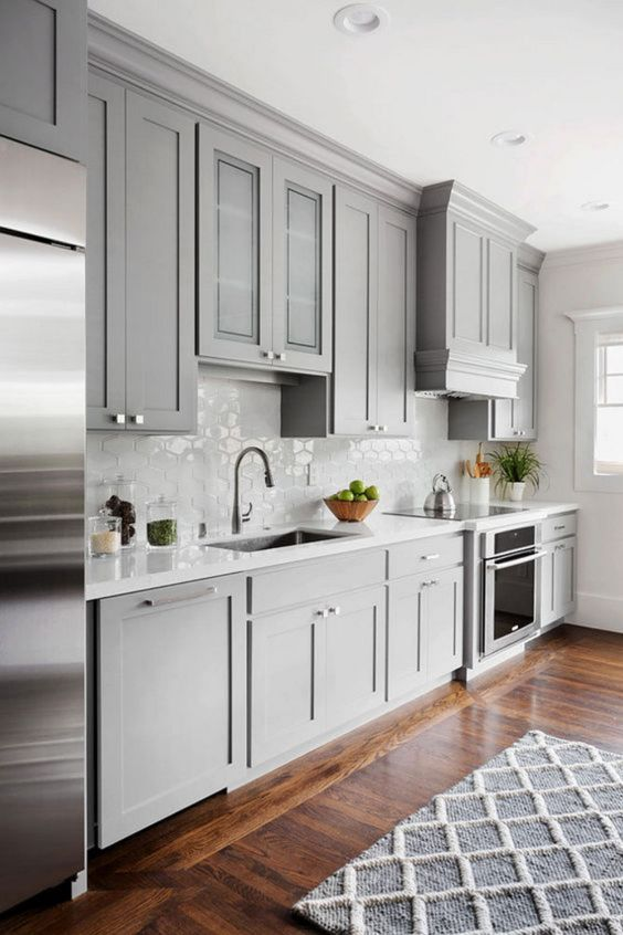 a light grey kitchen with shaker cabinets, a white Moroccan tile backsplash and white coutnertops plus stainless steel touches