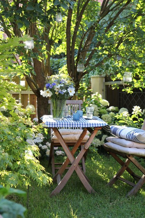 a little garden dining space on a green lawn, under the trees, with hanging candleholders and gold wooden chair plus cool textiles