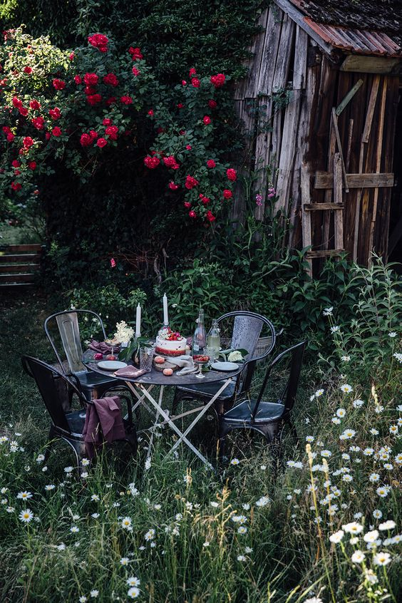 a little garden eating nook with a metal table and some meatching chairs plus blankets created in blooming surroundings