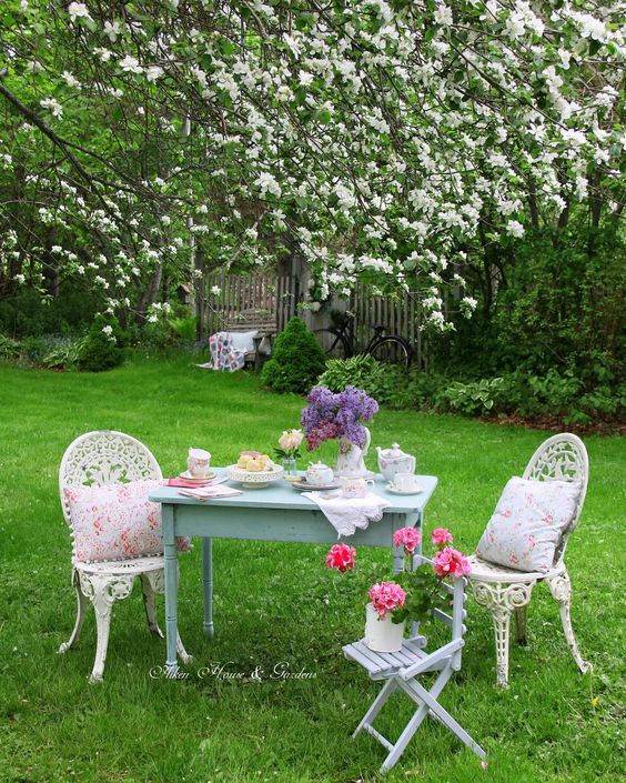 a little vintage tea space under the trees, with a blue table and vintage chairs plus floral porcelain