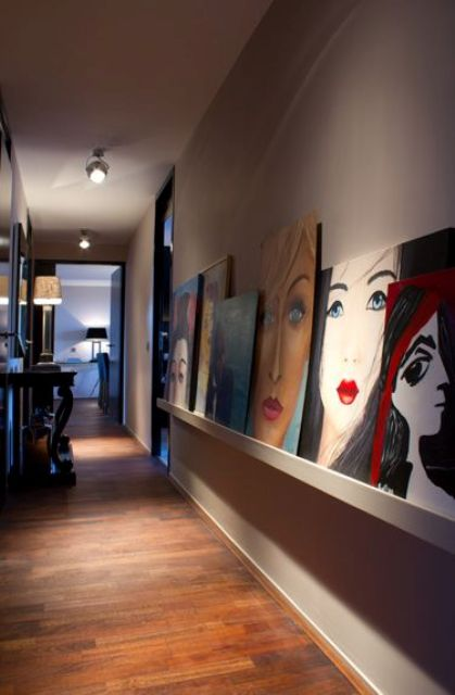 a long ledge with statement oversized artworks that make this corridor very special and very eye-catchy