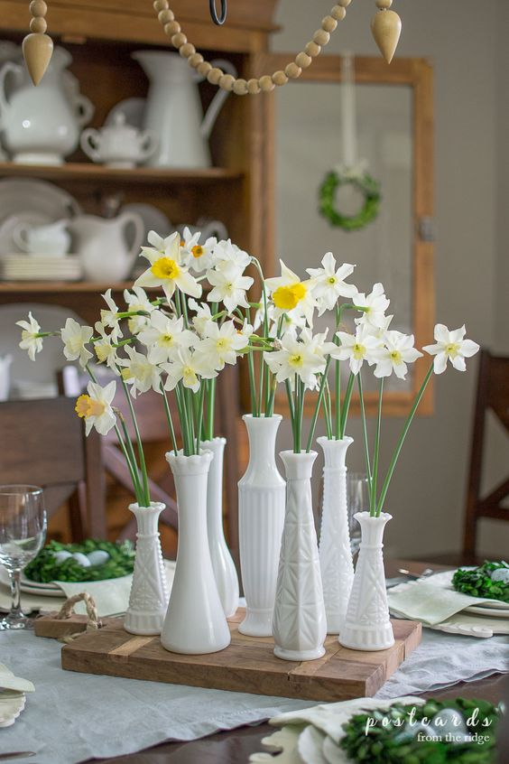 a lovely and simple spring cluster centerpiece of mismatching vases with daffodils placed on a wooden board