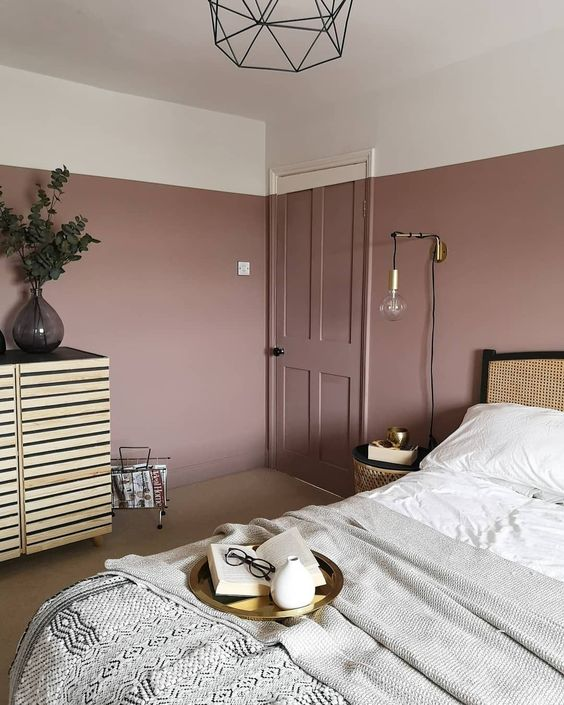 a lovely bedroom with mauve walls, a rattan bed, a wooden sideboard, neutral bedding and touches of gold