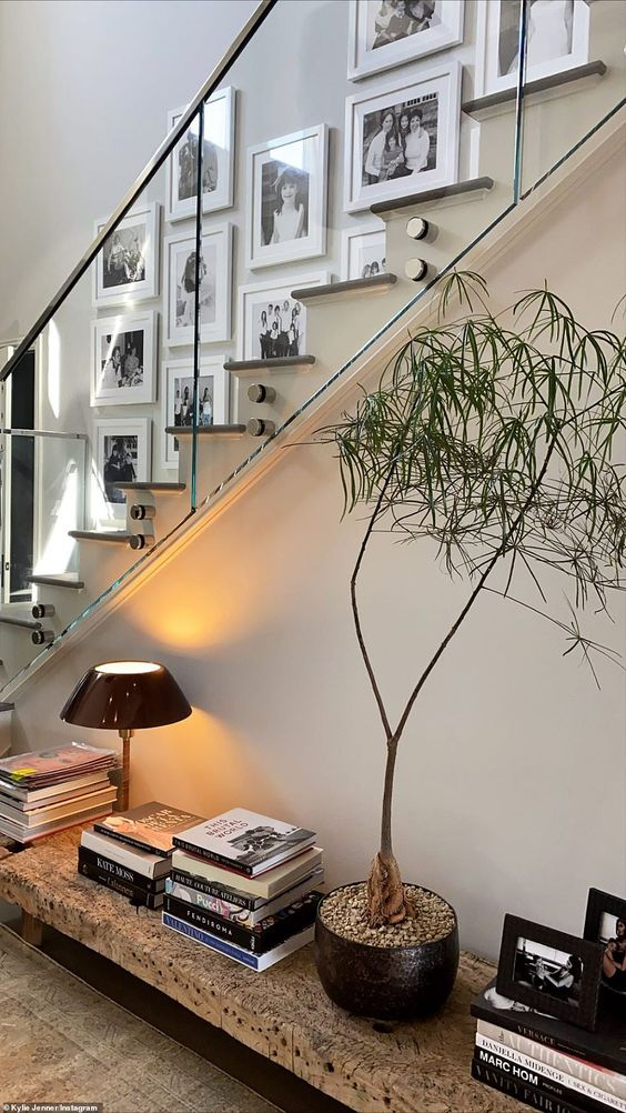 a lovely black and white free form gallery wall with matching white frames brings style and chic to this stairway space