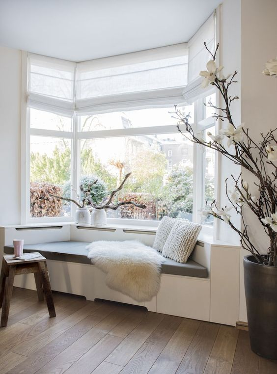 a lovely bow window with a windowsill daybed with pillows make up a lovely reading nook in the space
