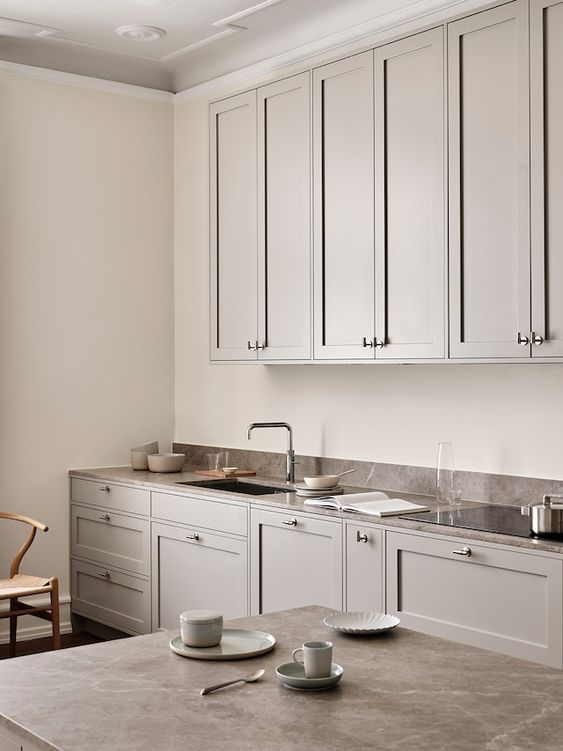 a lovely dove grey shaker style kitchen with dark quartz countertops and vintage-style fixtures is welcoming and inviting