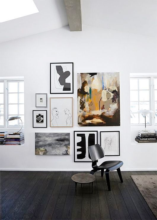 a lovely modern gallery wall with a non-framed central artwork and thin framed other works is chic