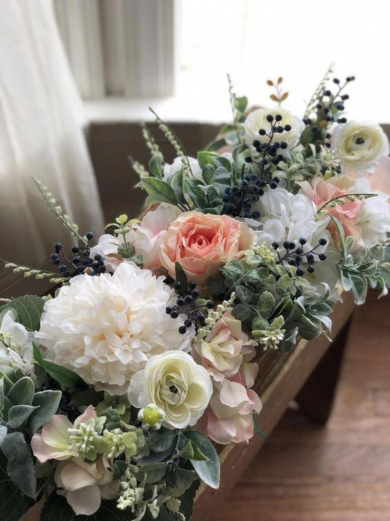 a lush faux floral arrangement of white, pastel blooms, greenery and berries in a wooden box