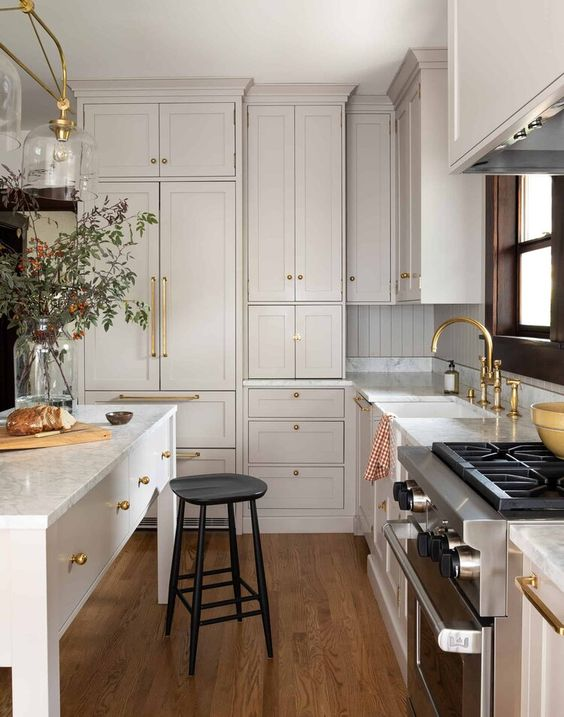 a marvelous creamy kitchen with shaker style cabinets, white quartz countertops and a beadboard backsplash plus gold touches