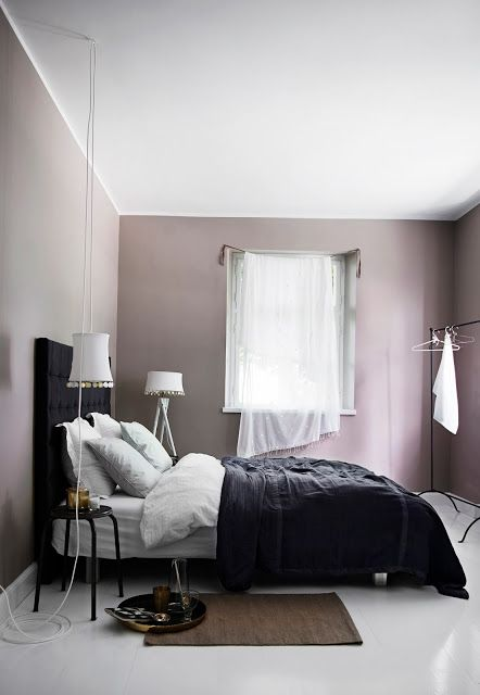 a mauve Scandinavian bedroom with a black bed, black and white bedding, neutral curtains and white lamps