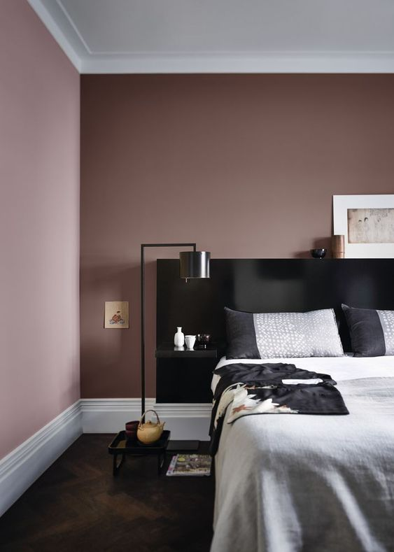 a mauve bedroom with a black bed, grey and black bedding, black floor lamps and pretty artworks