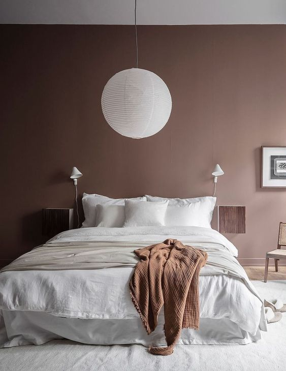 a mauve bedroom with a cozy white bed, mauve nightstands, a paper lamp and a rust blanket