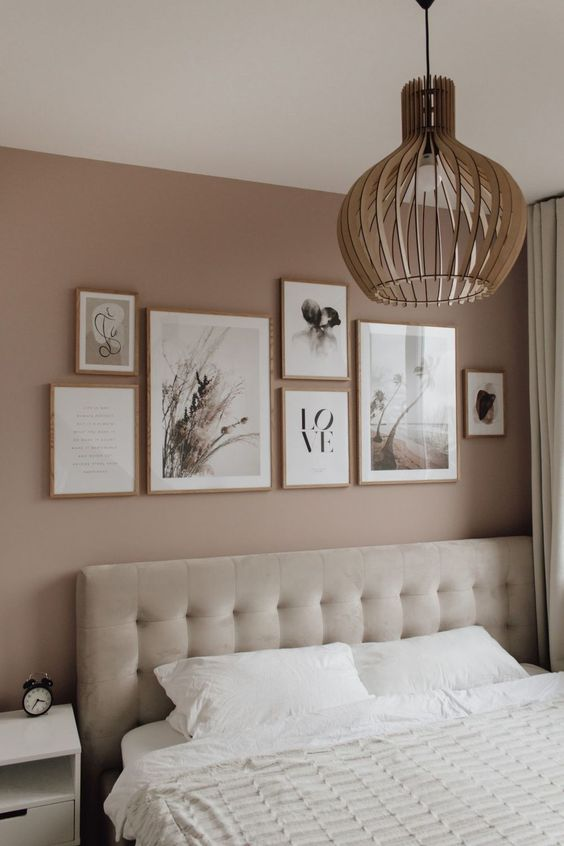 a mauve bedroom with a creamy upholstered bed, a nightstand, a lovely gallery wall and a plywood pendant lamp