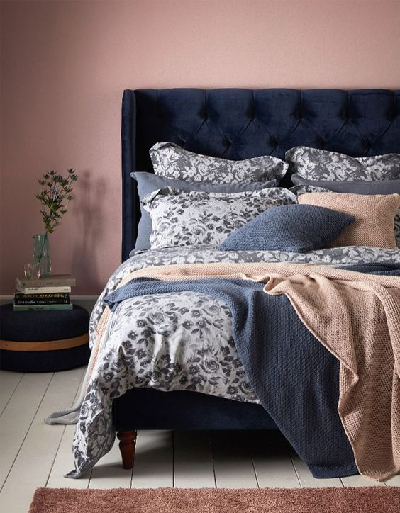a mauve bedroom with a navy velvet bed, blue and tan bedding with a floral print, a navy ottoman