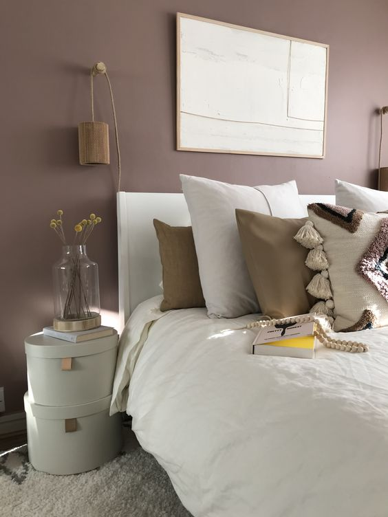 a mauve bedroom with a white bed with neutral boho bedding, stacked boxes, wooden sconces and a statement artwork