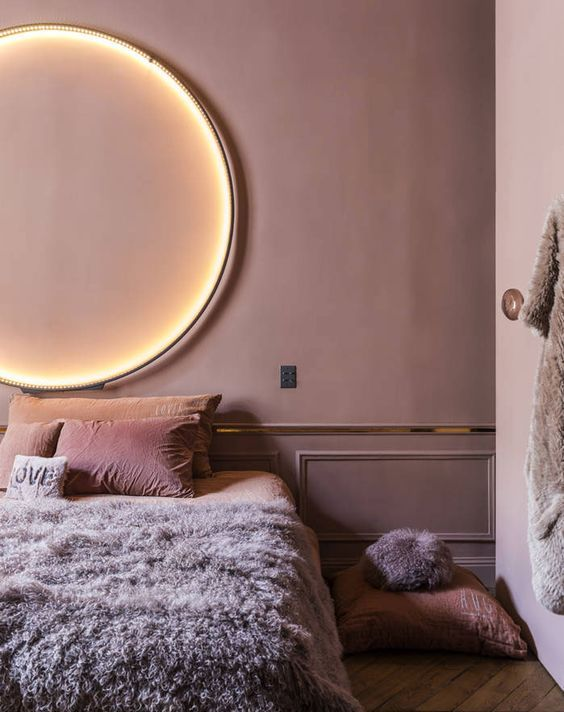 a mauve bedroom with gold edge, a lit up circle lamp and pink and lavender bedding is very refined