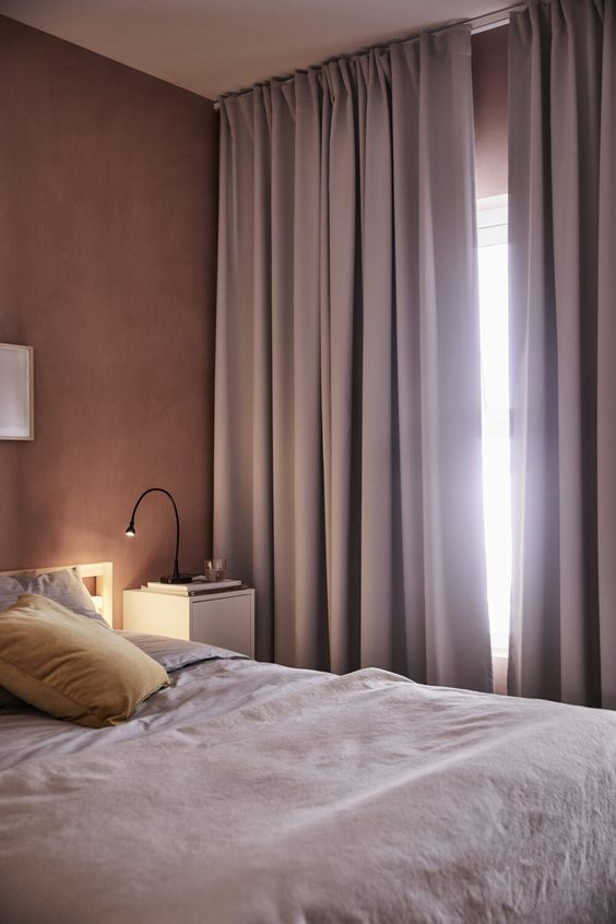 a mauve bedroom with mauve walls, a bed with lavender bedding, lavender curtains and black table lamps